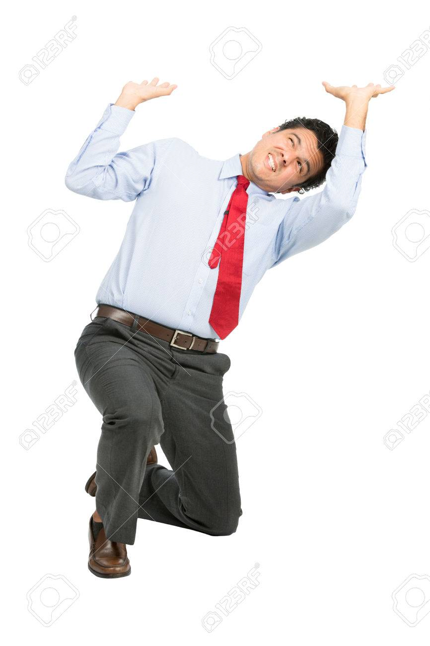 A stressed latino businessman in business clothes on knee using arms pushing up, resisting against crushing imaginary weight, object under heavy stress, feeling pressure. Isolated on white background - 44195194