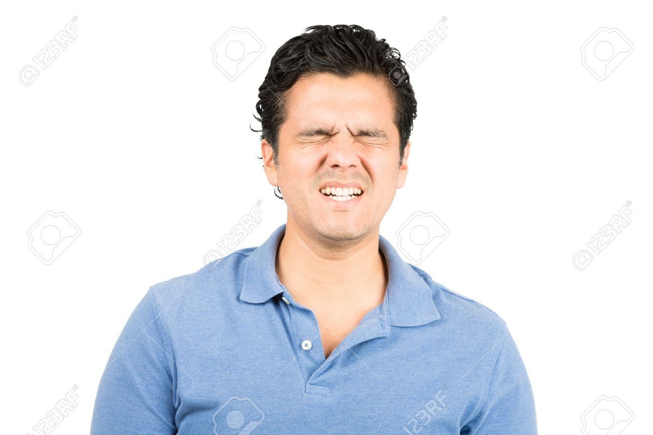 Good looking hispanic male in blue collared shirt eyes closed, grimacing with pained facial expression of suffering, pain, hurt and agony - 44228200