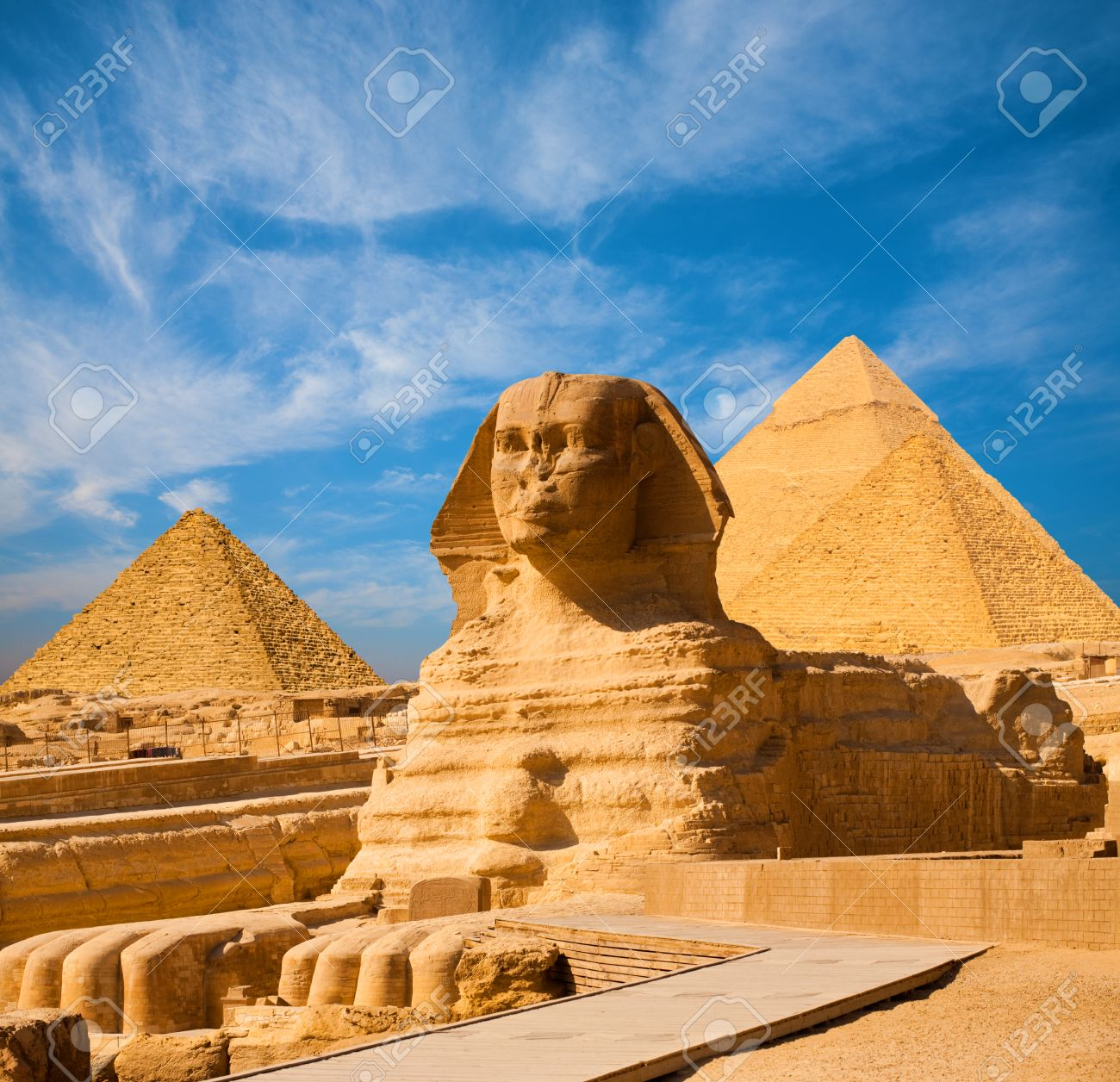Egyptian Great Sphinx full body portrait with head, feet with all pyramids of Menkaure, Khafre, Khufu in background on a clear, blue sky day in Giza, Egypt empty with nobody. copy space - 65834164