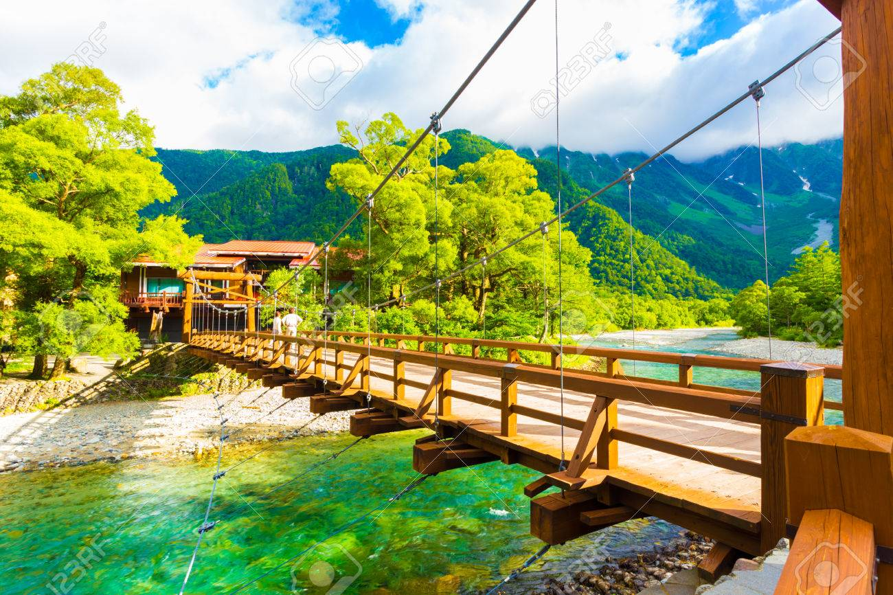 View of Mount Hotaka behind rustic Kappa Bashi Bridge over clear turquoise water of Azusa River in pristine Japanese Alps village of Kamikochi, Nagano Prefecture, Japan - 67106905