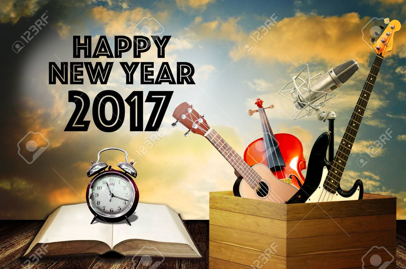 Alarm clock on open book and music instrument with happy new stock alarm clock on open book and music instrument with happy new year greeting word stock photo m4hsunfo