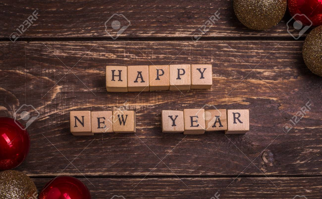 happy new year christmas card small wooden letters on wood cubes standing on dark rustic