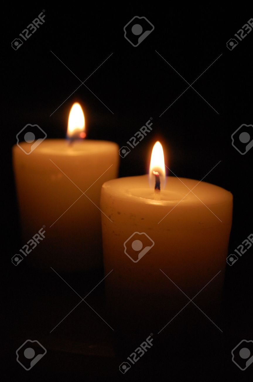 Two Lit Candles Glowing In The Dark Stock Photo, Picture And ...