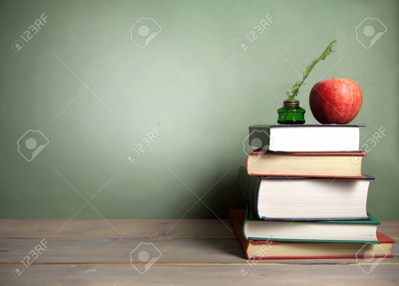 Stack Of Books With Apple And Quill Next To A Chalkboard Background Stock Photo