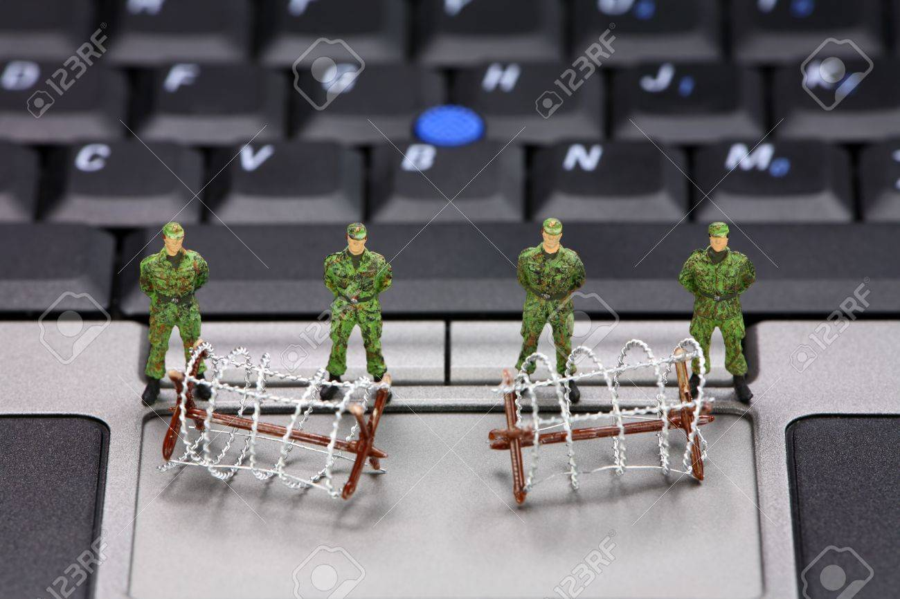 Miniature military soldiers and barbed wire are guarding a laptop from viruses, spyware and identity thieves. Computer security concept. Stock Photo - 8949433