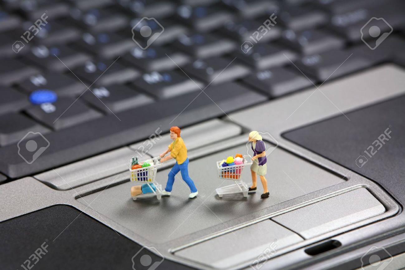 Miniature shoppers with shopping carts on a laptop touch pad mouse. Online shopping concept. Stock Photo - 8954532