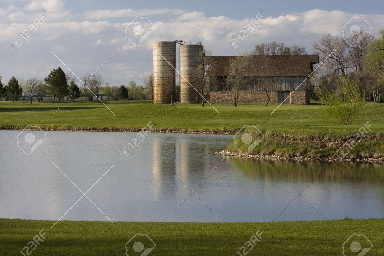 barn with two silos surrounded by green meadows, lake and houses - old farm turned into a golf course Stock Photo - 3057424