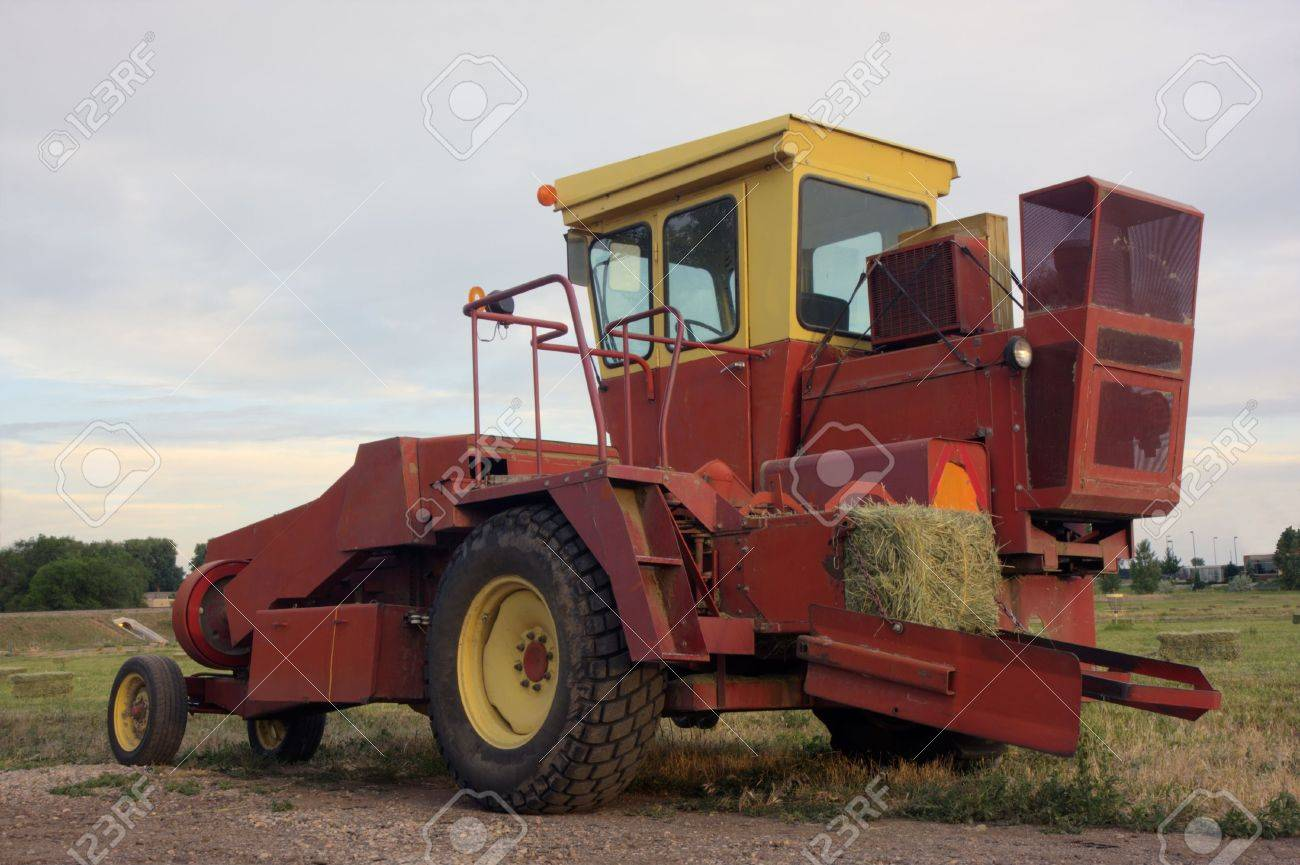 a small square hay baler in a field after harvest, HDR image