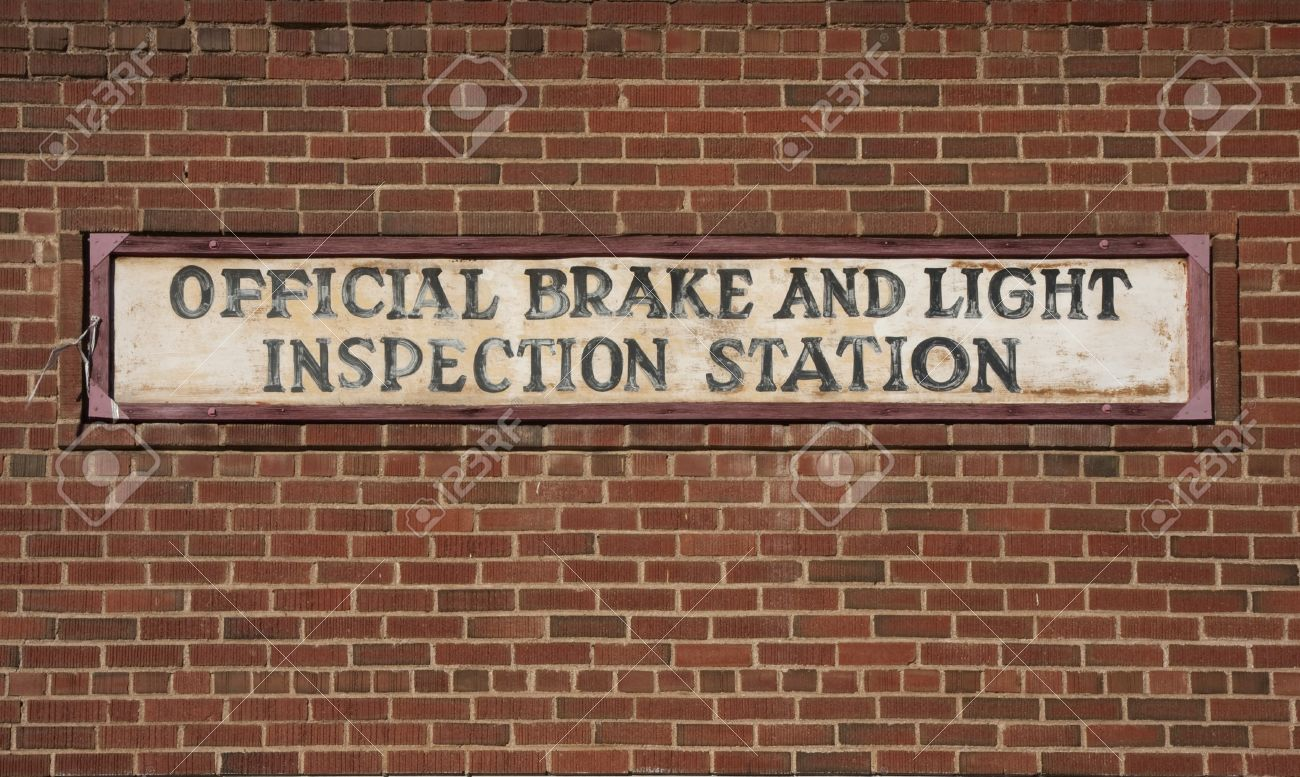 Stock Photo   Vintage Brake And Light Inspection Sign Against Red Brick  Wall From An Old Garage