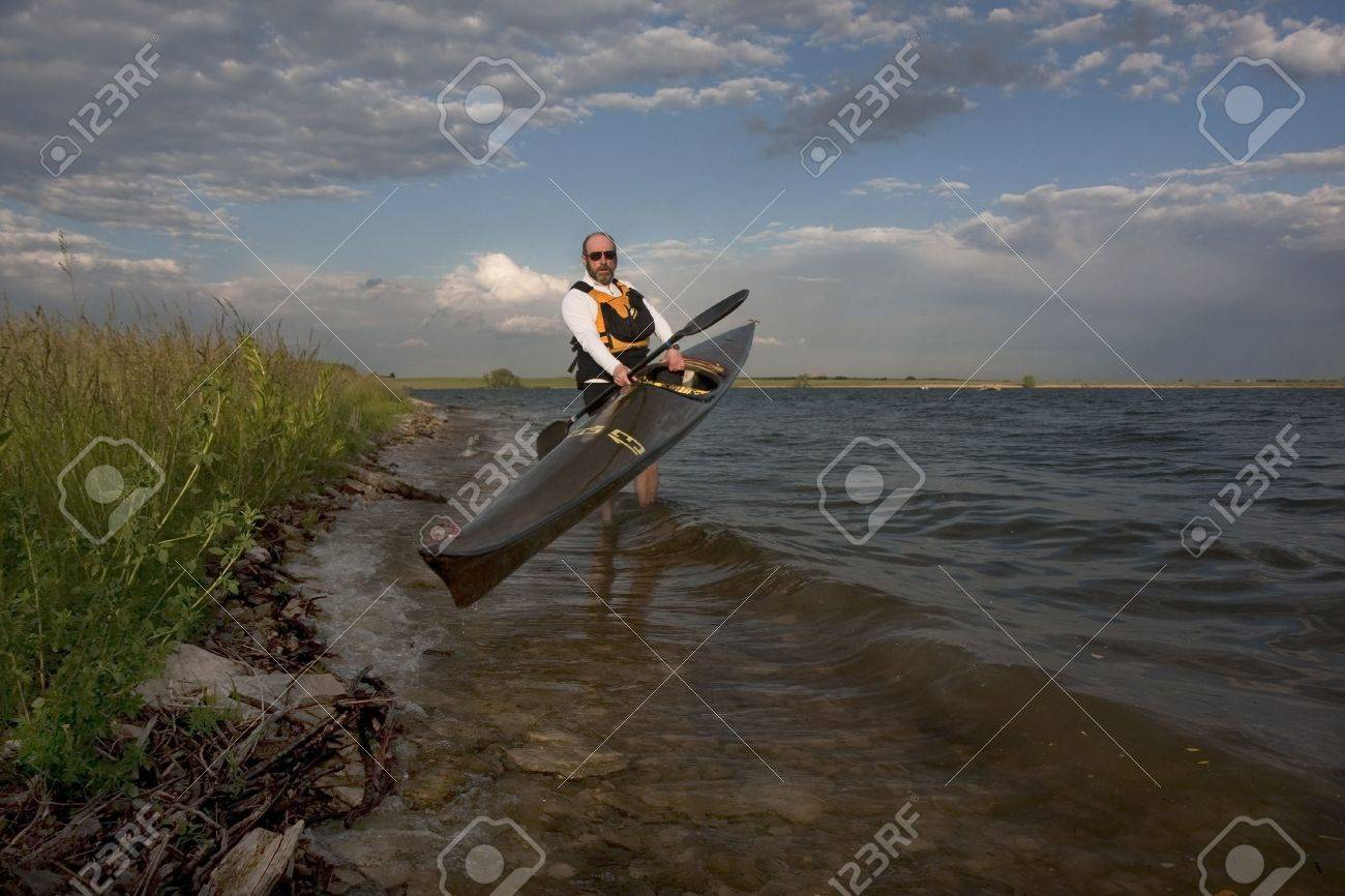 mature paddler launching long racing carbon fiber kayak on a lake with grassy and rocky shore in northern Colorado, thirteen - temporary race number placed on deck by myself Stock Photo - 5103735
