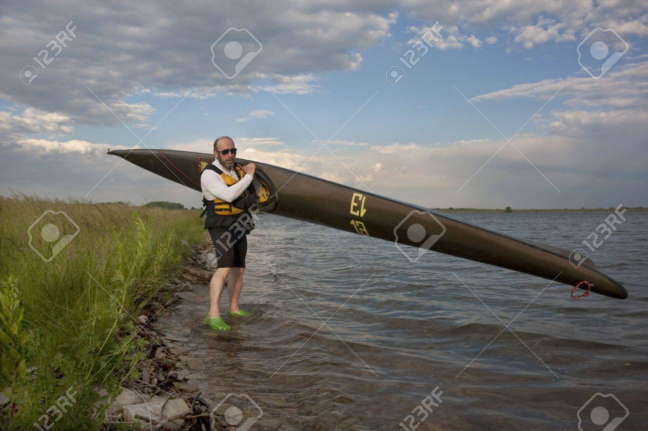 mature paddler is carrying  a long racing carbon fiber kayak to launch it on a lake with grassy and rocky shore in northern Colorado (thirteen - temporary race number placed on deck by myself) Stock Photo - 5103736