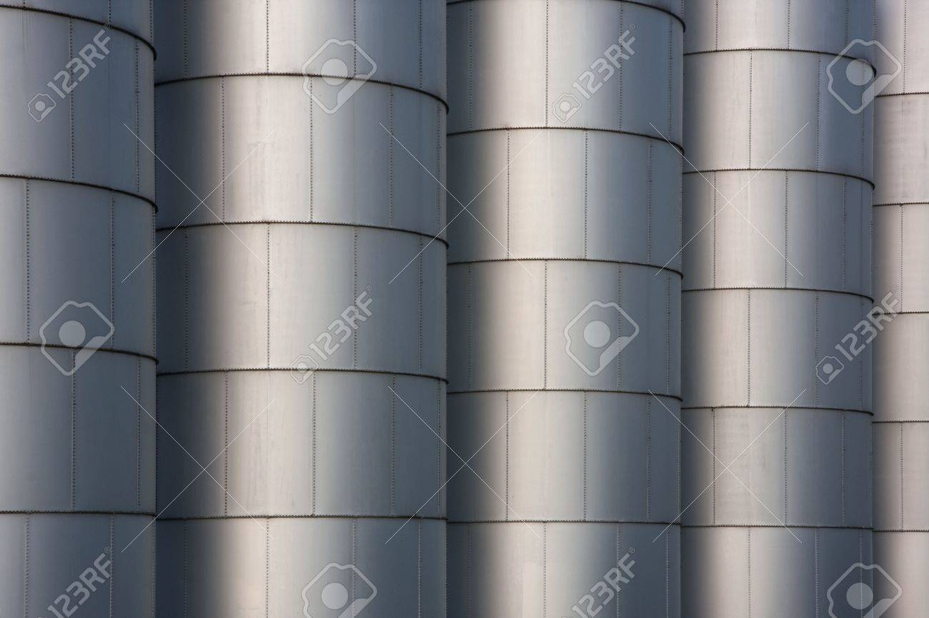 a row of metal round grain storage bins with rivets - industrial