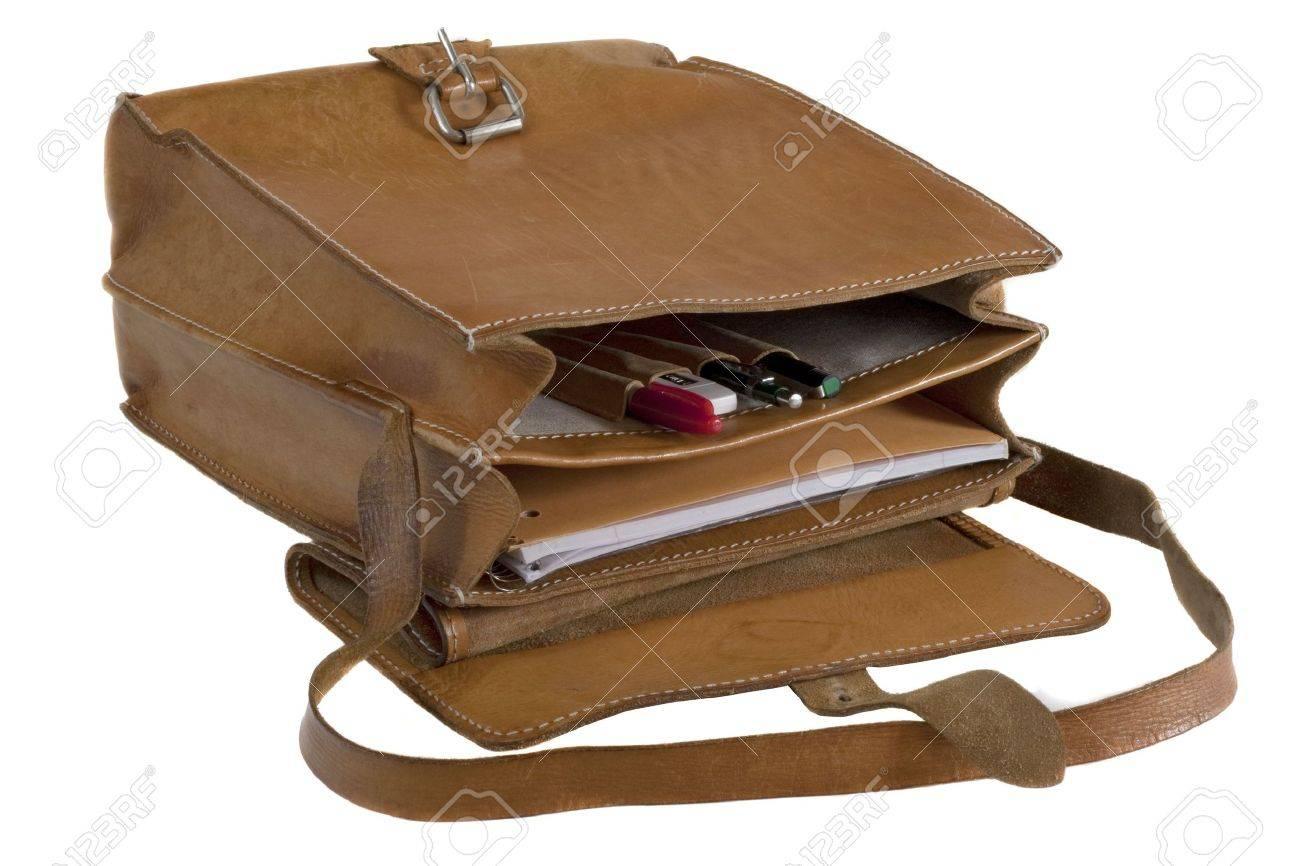 5d875ab37c7 Oude leren schooltas met krassen en vlekken - geopend waaruit pennen en  notebook, geïsoleerd op