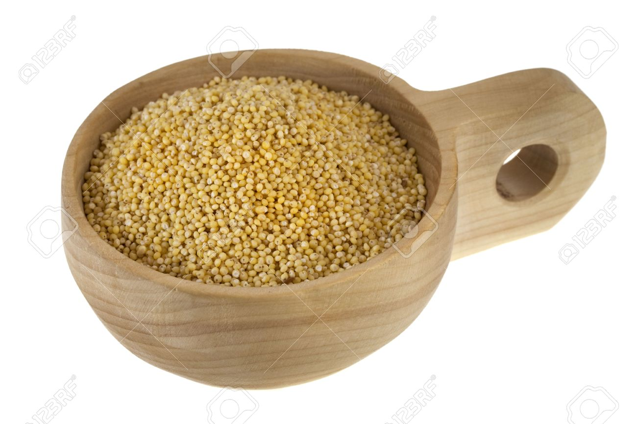hulled millet grain on a rustic, wooden scoop or bowl, isolated on white Stock Photo - 6392206