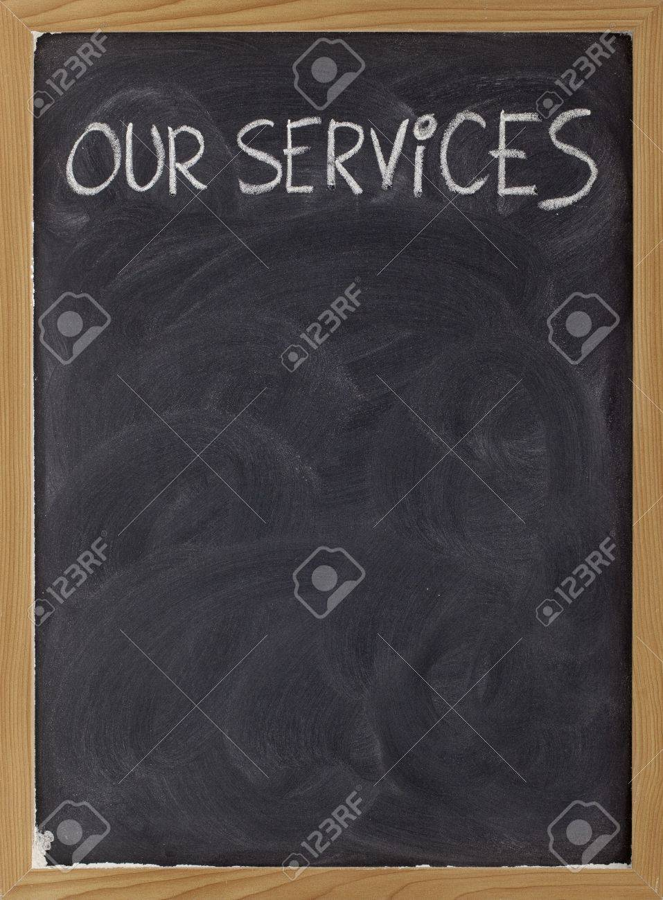 our services - white chalk handwriting on blackboard with eraser smudges, copy space below Stock Photo - 6564743