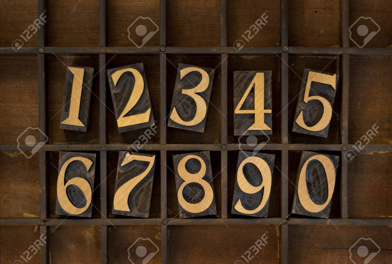 ten arabic numerals from zero to nine, vintage wood letterpress blocks stained by black ink in old typesetter case with dividers, types flipped horizontally Stock Photo - 6790280