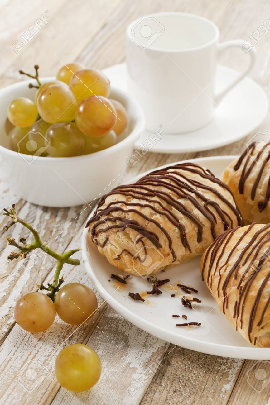 mini chocolate croissants, grapes and coffee cup on a rustic wood table Stock Photo - 9565965