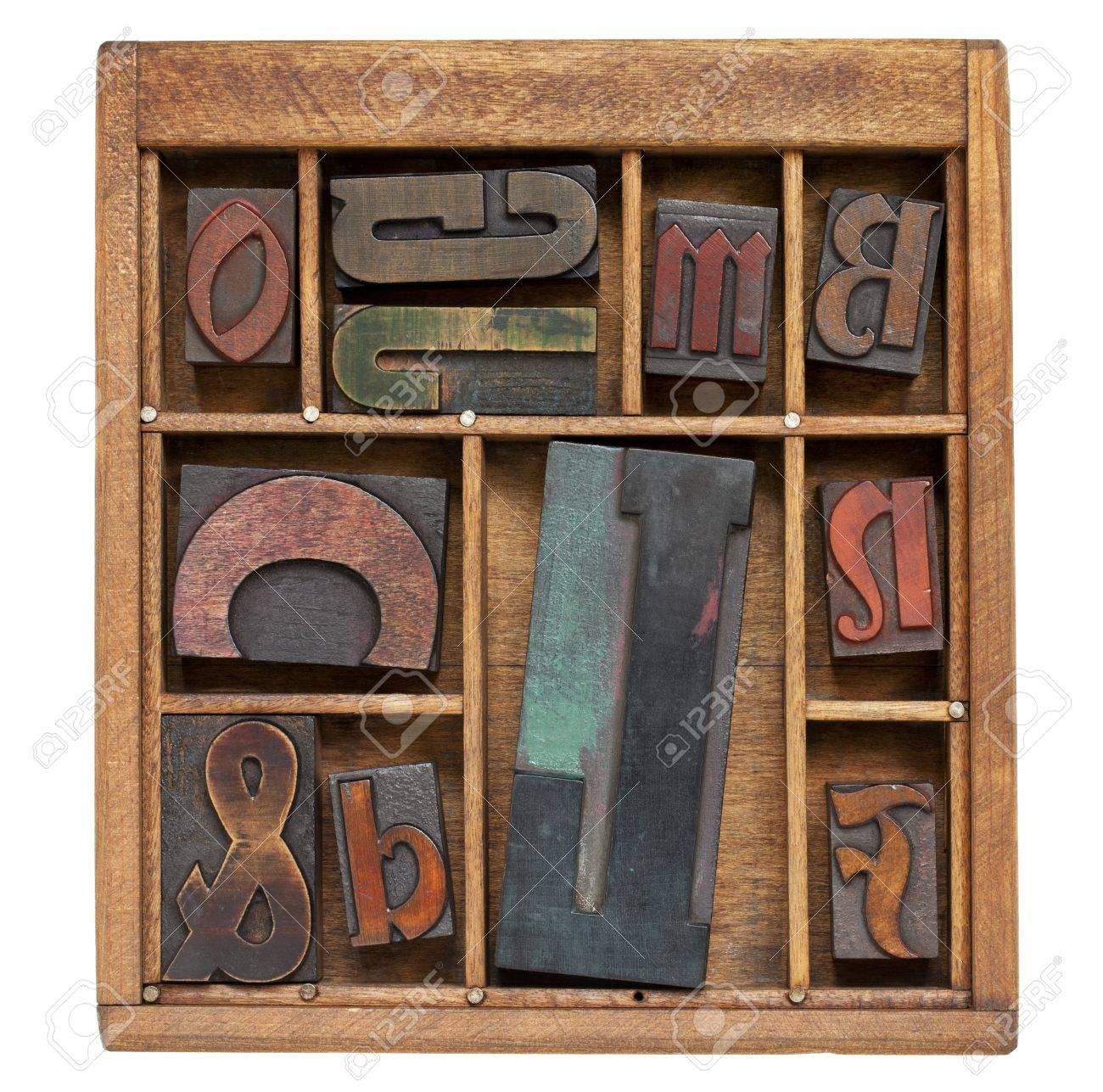 a variety of vintage letterpress printing blocks with big letter L in a small wooden typesetter box with dividers, isolated on white Stock Photo - 9739571
