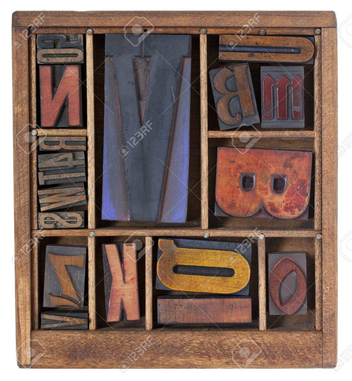 a variety of vintage letterpress printing blocks with big letter V in a small wooden typesetter box with dividers, isolated on white Stock Photo - 9968823