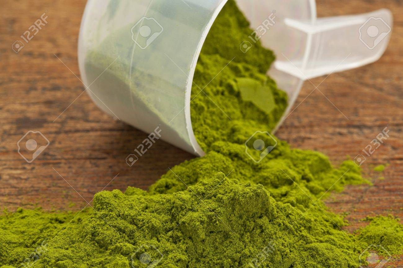 wheatgrass powder spilling of a plastic measuring scoop against grunge wood background Stock Photo - 13762473