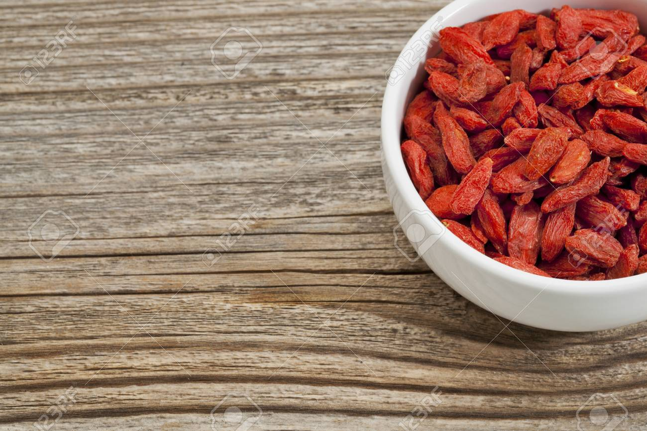 goji berries - white ceramic bowl on a grained wood, copy space Stock Photo - 14384452