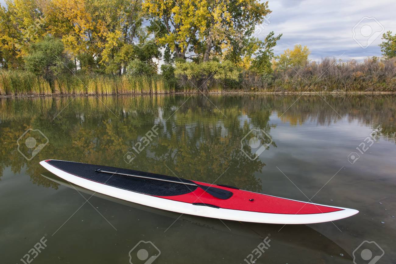 stand up paddleboard with paddle on a calm lake in fall scenery Stock Photo - 15416370