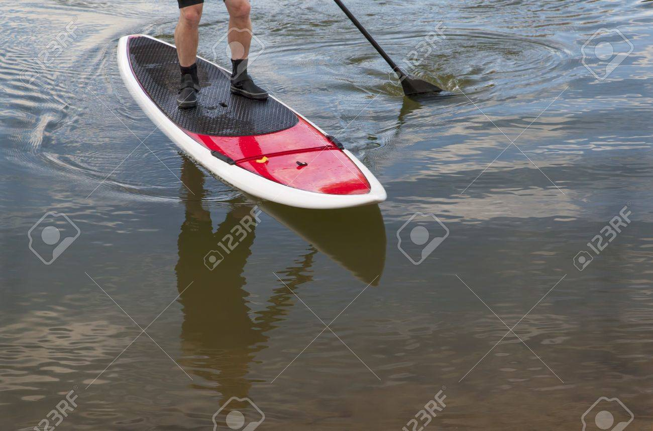 paddling stand up paddleboard on a lake - feet and legs of male paddler Stock Photo - 15887235