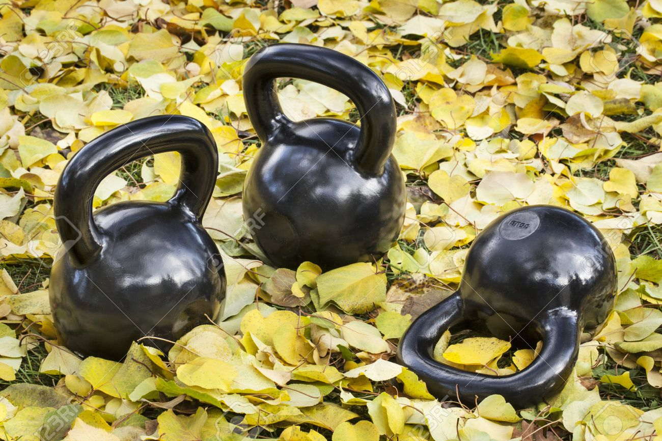 three heavy iron  kettlebells outdoors in a fall scenery  - outdoor fitness concept Stock Photo - 16012806