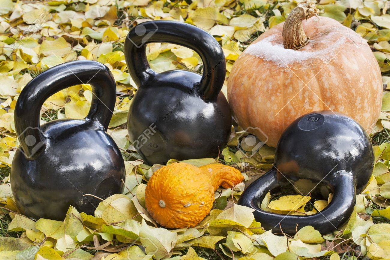 three heavy iron  kettlebells outdoors in a fall scenery  with pumpkin and squash - outdoor fitness concept Stock Photo - 16012807