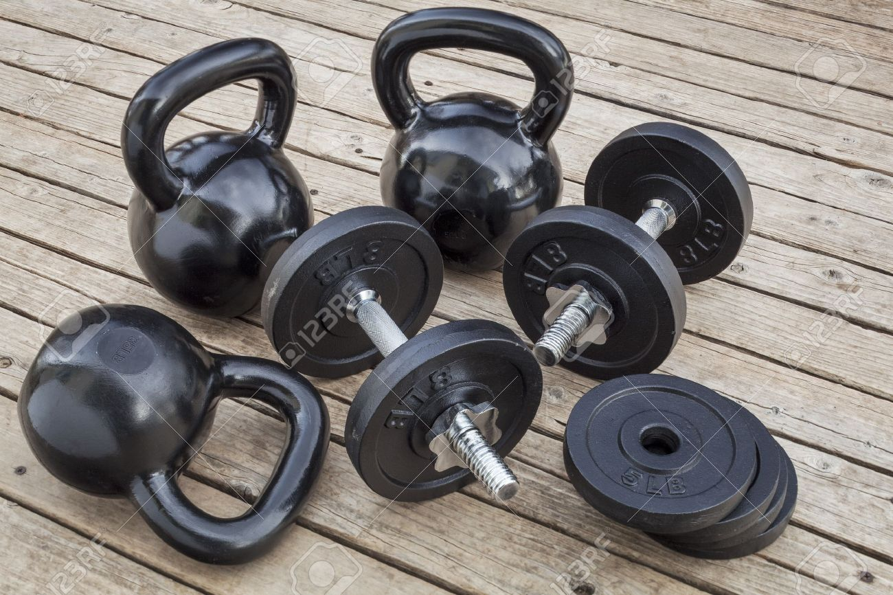 exercise weights - kettlebells and dumbbells on a wooden deck - a home gym concept Stock Photo - 16529556