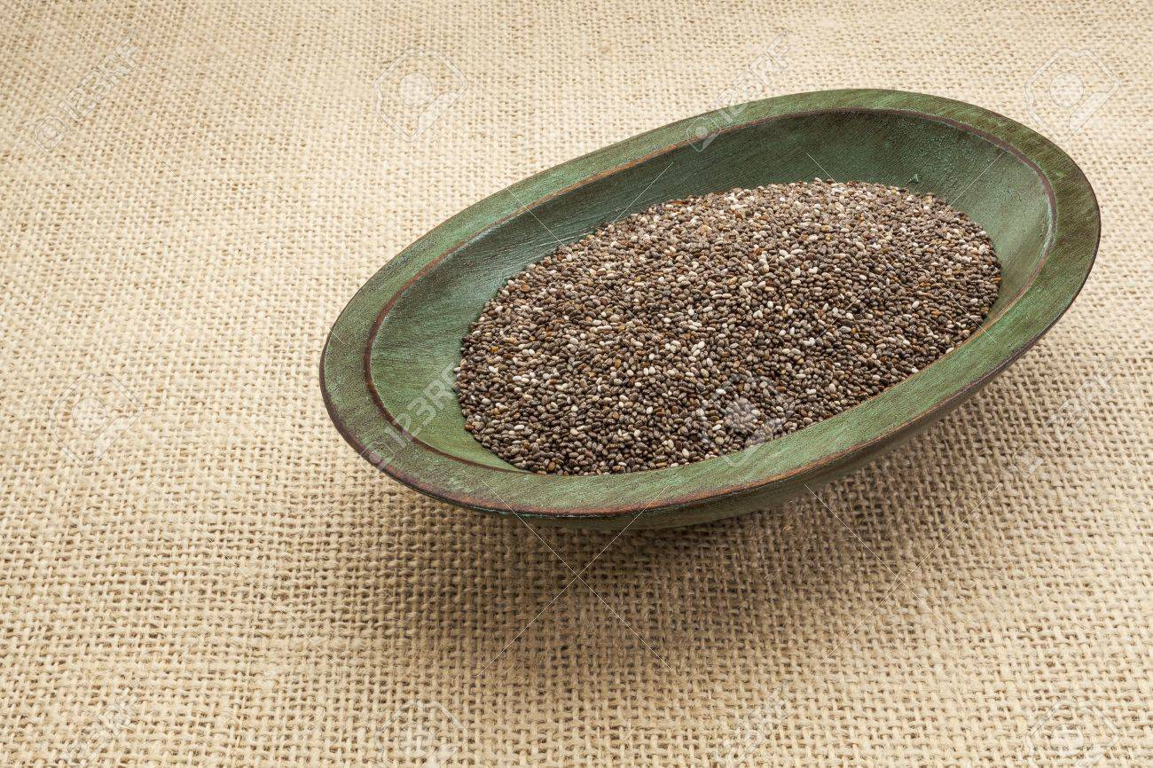 chia seeds in a rustic oval wood bowl against canvas Stock Photo - 17067702
