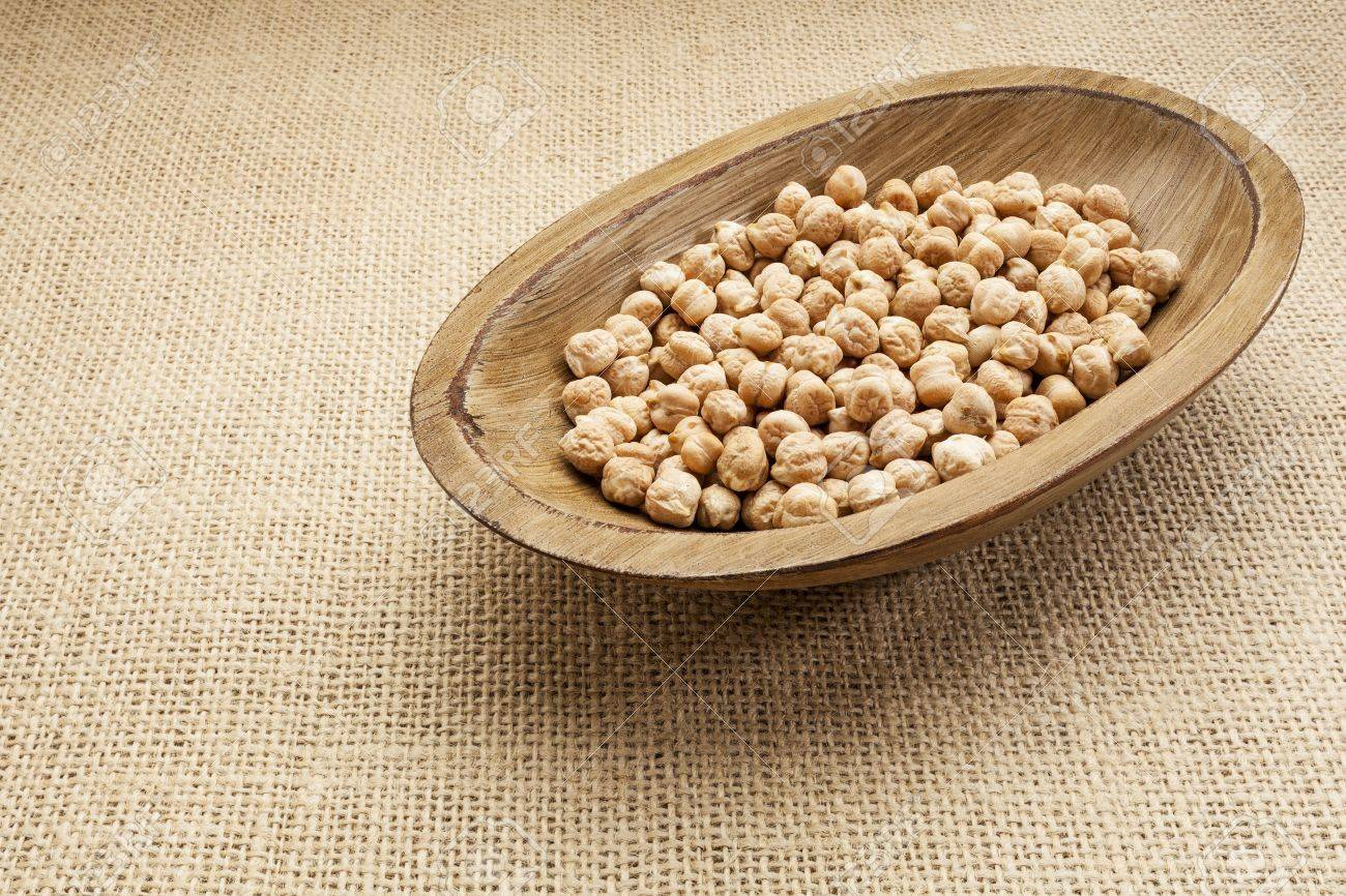 chickpea (garbanzo) beans in a rustic wood bowl against burlap canvas Stock Photo - 17113357