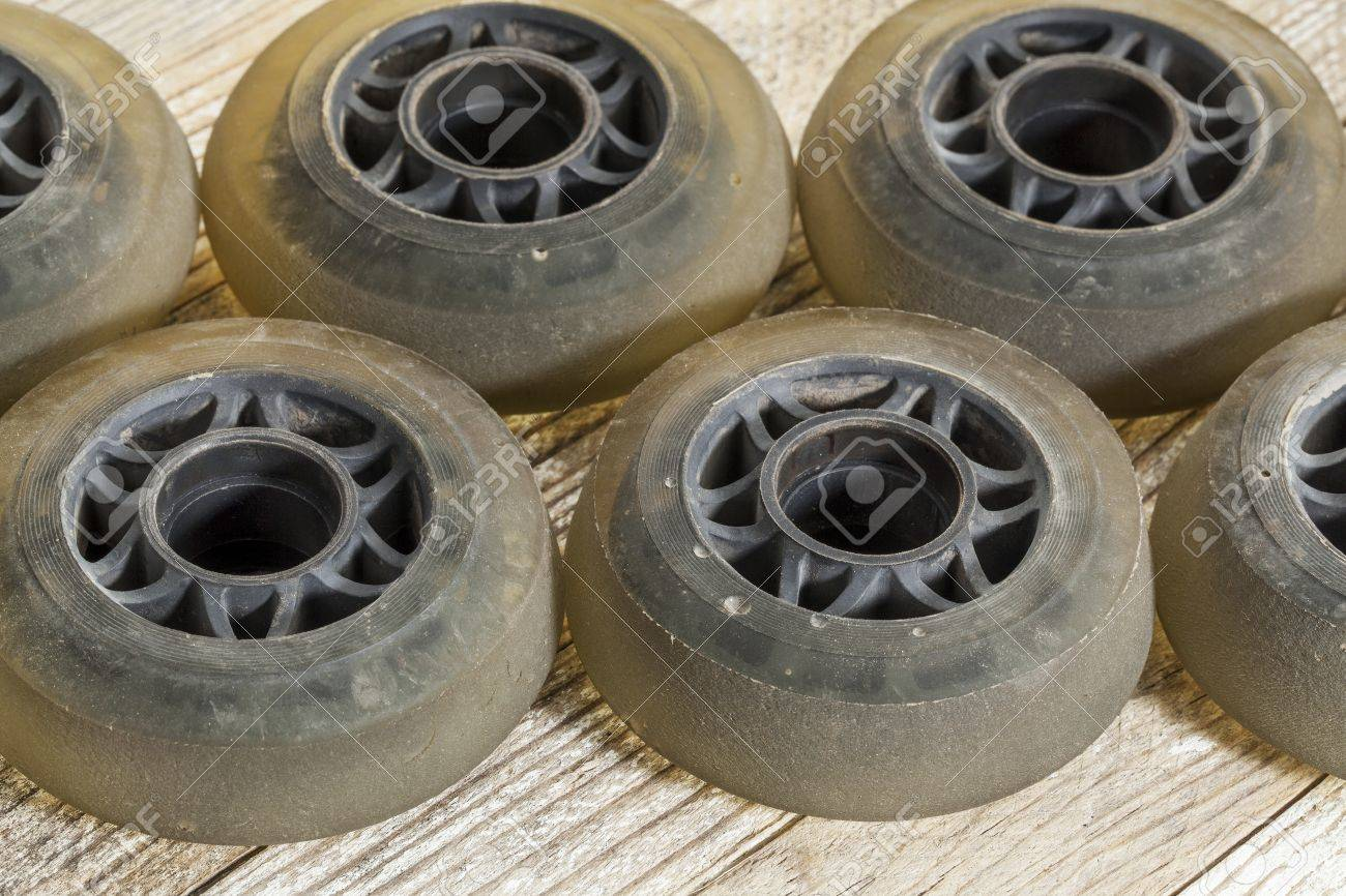 old worn out wheels for inline skating on wooden surface Stock Photo - 17668289