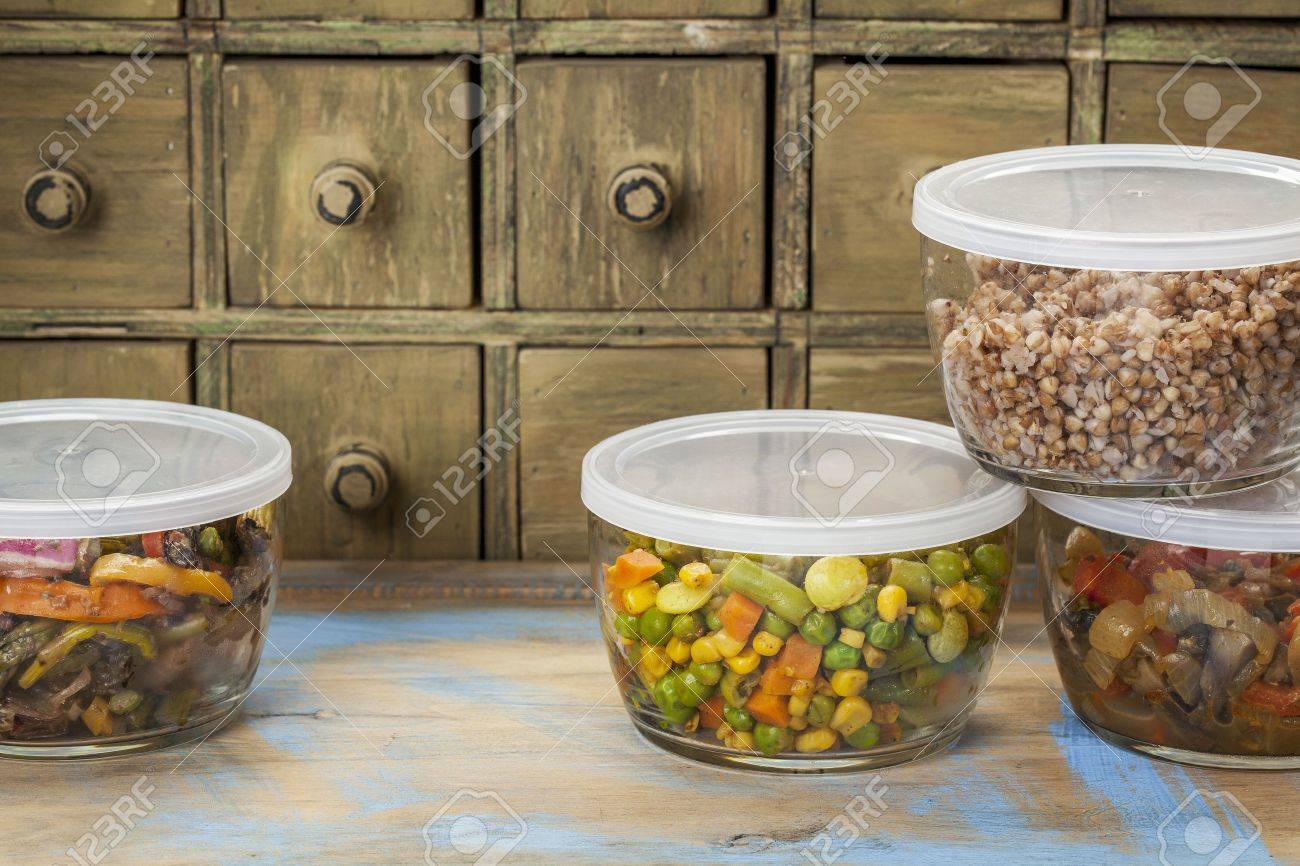 dinner leftovers (buckwheat kasha, vegetables, stir fry)  in glass  containers with drawer cabinet in background Stock Photo - 20832325