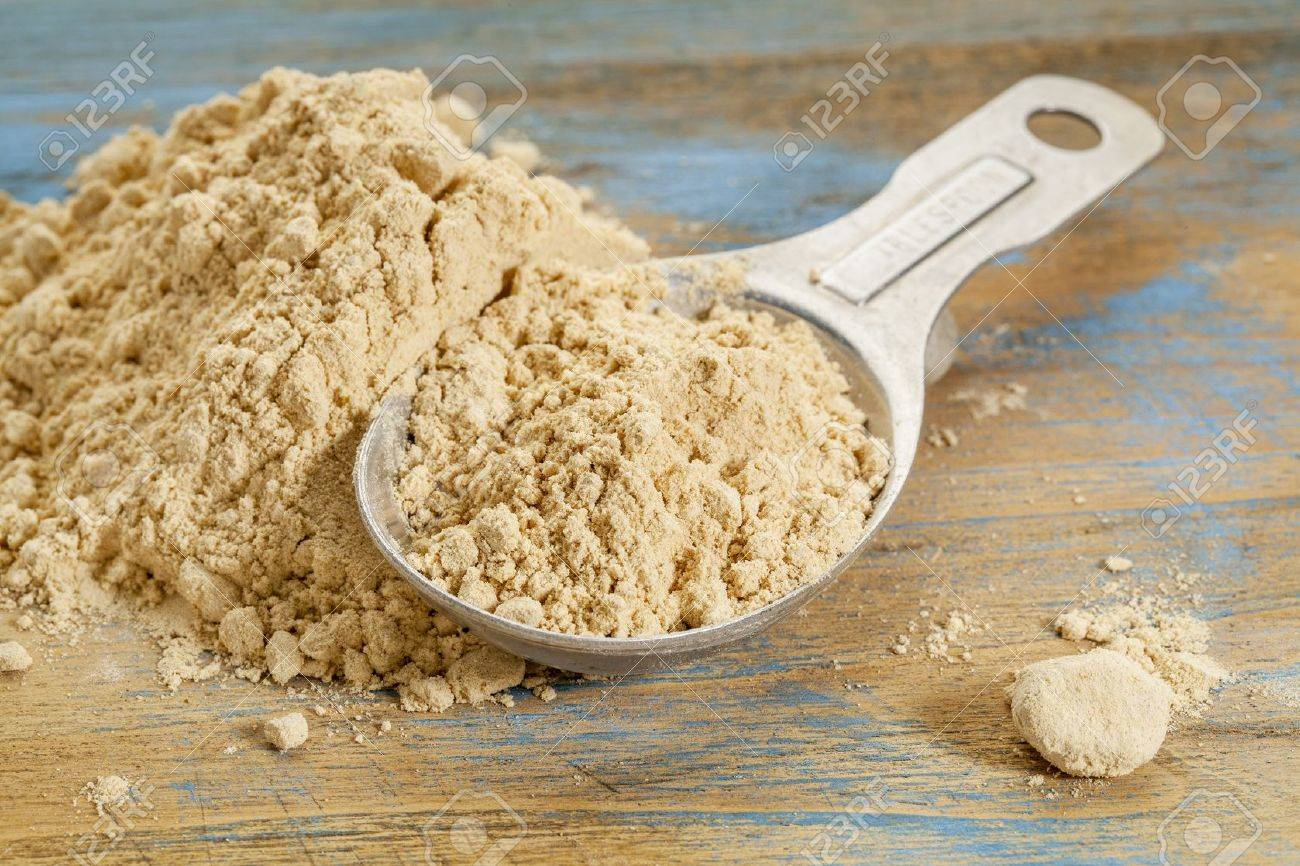 maca root powder - a measuring tablespoon and pile on wooden surface Stock Photo - 21642198