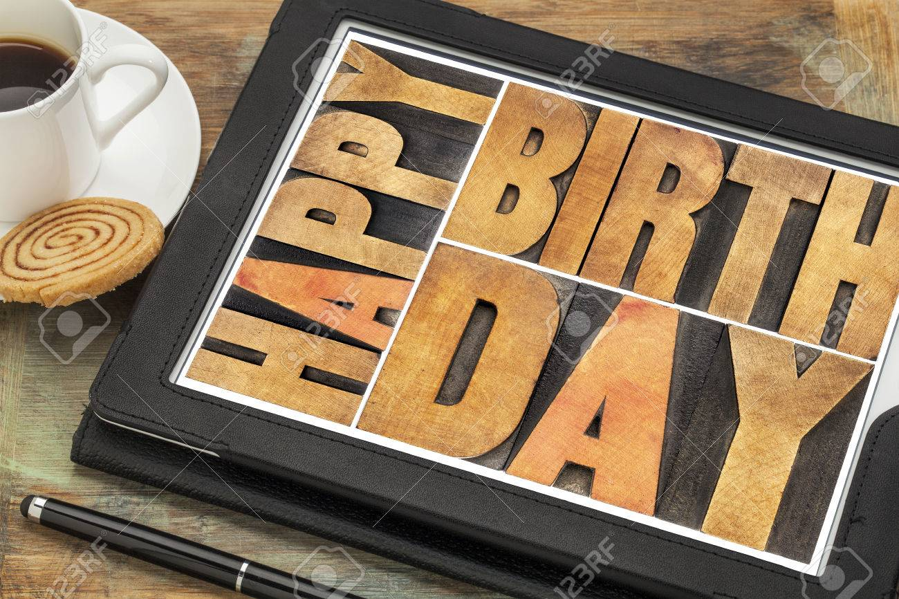 Happy birthday in letterpress wood type on digital tablet computer with stylus pen, coffee cup and cookie Stock Photo - 23313055
