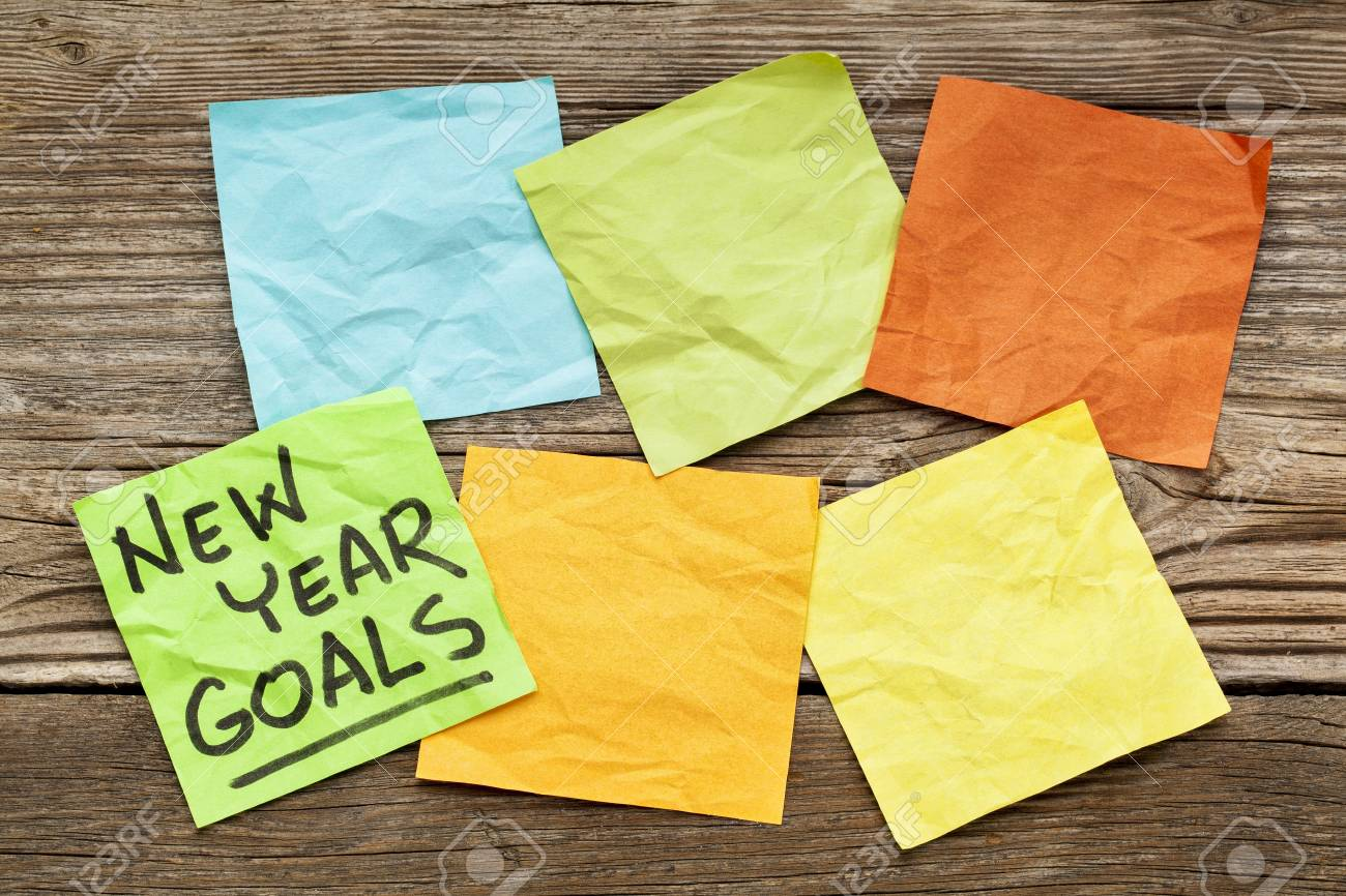 New Year goals - handwriting on a sticky note against grained wood with blank notes Stock Photo - 24732445