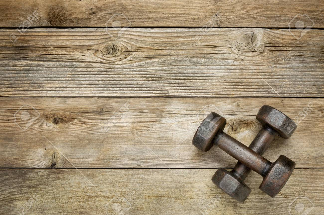 a pair of vintage iron rusty dumbbells on a weathered wood background with a copy space - 28217980