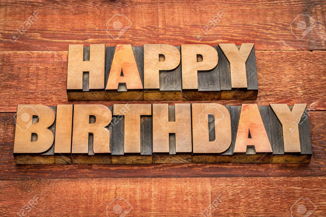 Happy Birthday Greetings In Letterpress Wood Type Against Rustic Red Painted Barn Stock Photo
