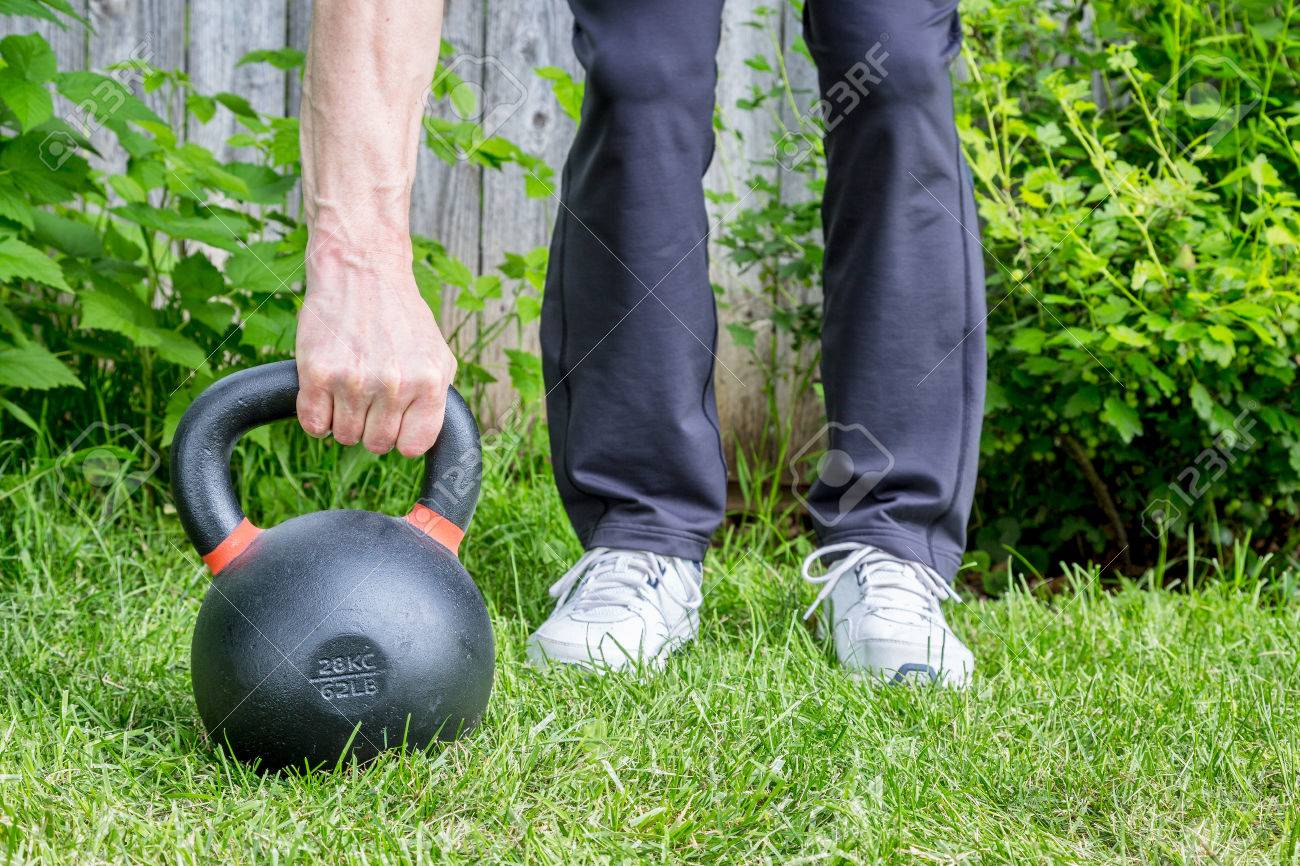 outdoor fitness concept weight training with a heavy iron