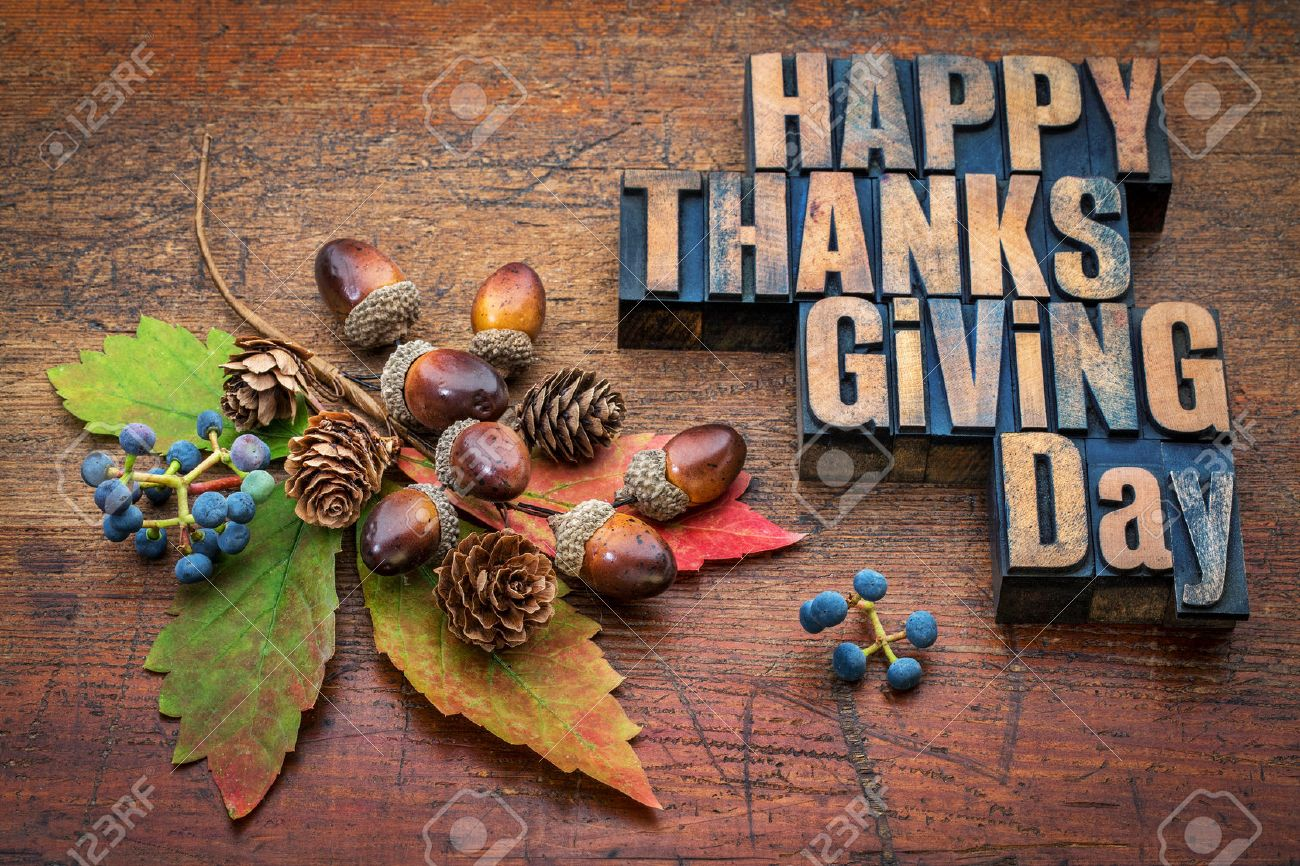 Happy Thanksgiving Day - text in vintage letterpress wood type with fall decoration (acorns, cones, leaf and vine berries) against rustic wood Stock Photo - 44977011