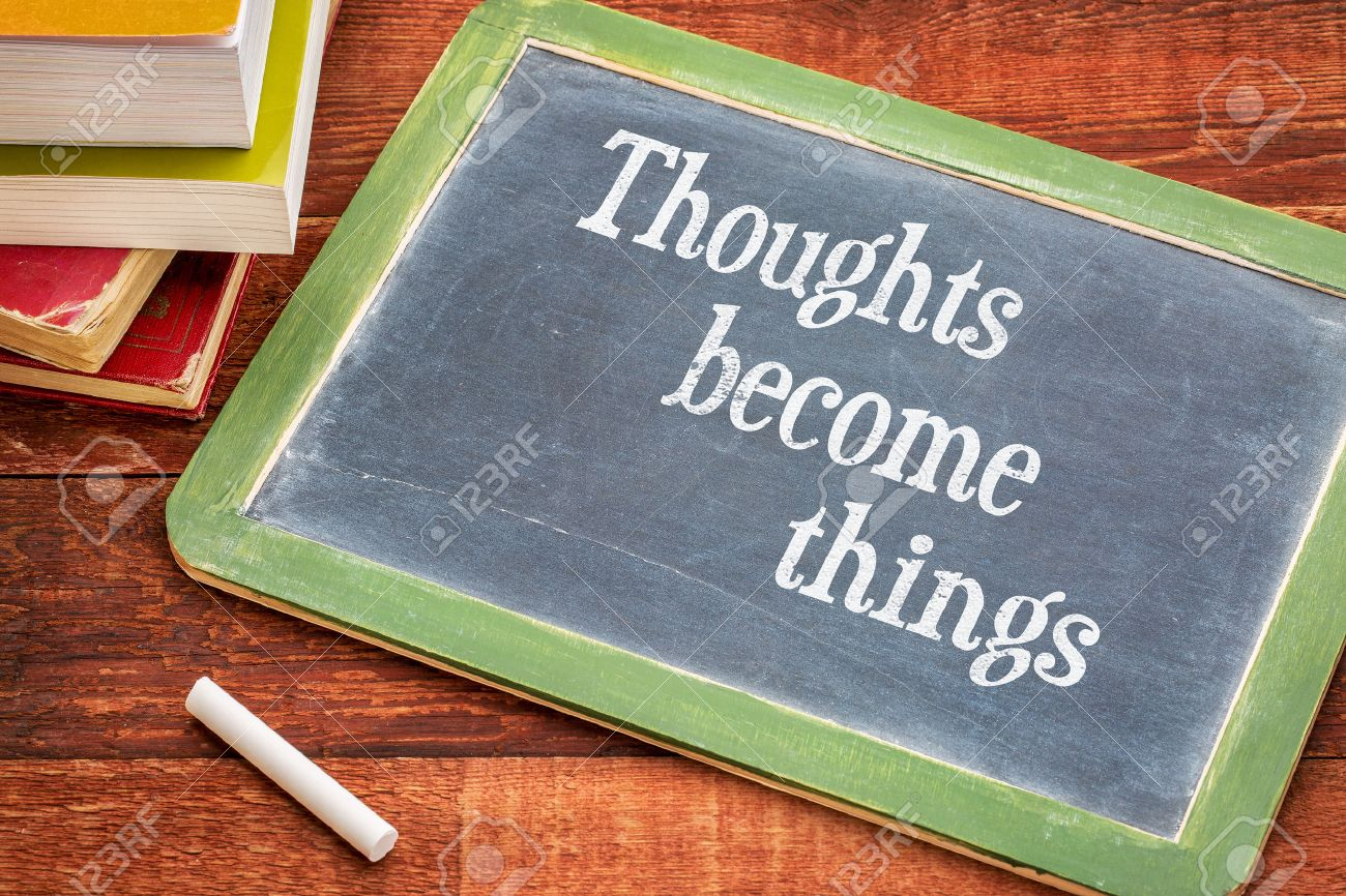 thoughts become things - law of attraction concept - inspirational text on a slate blackboard with a white chalk and a stack of books against rustic wooden table Stock Photo - 45296463