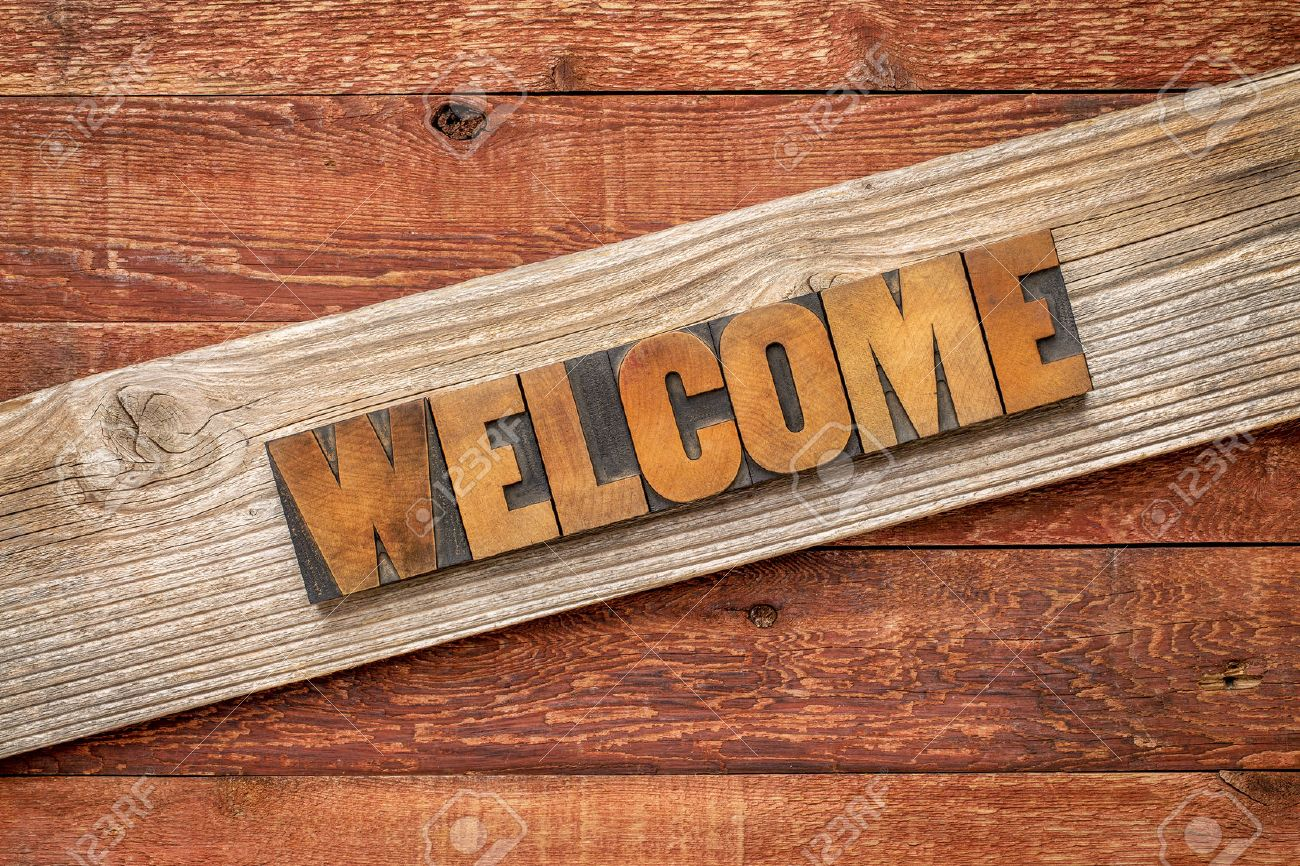 rustic welcome sign - letterpress wood type over grained cedar plank against red barn wood Stock Photo - 46177312