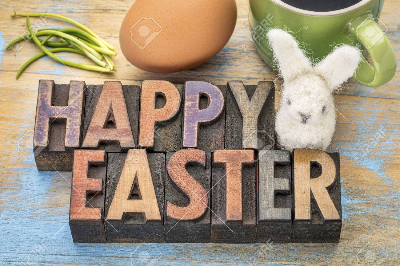 Happy Easter - greeting card, text in letterpress wood type printing blocks stained by color inks with an egg,woolen bunny and green chives Stock Photo - 52657475