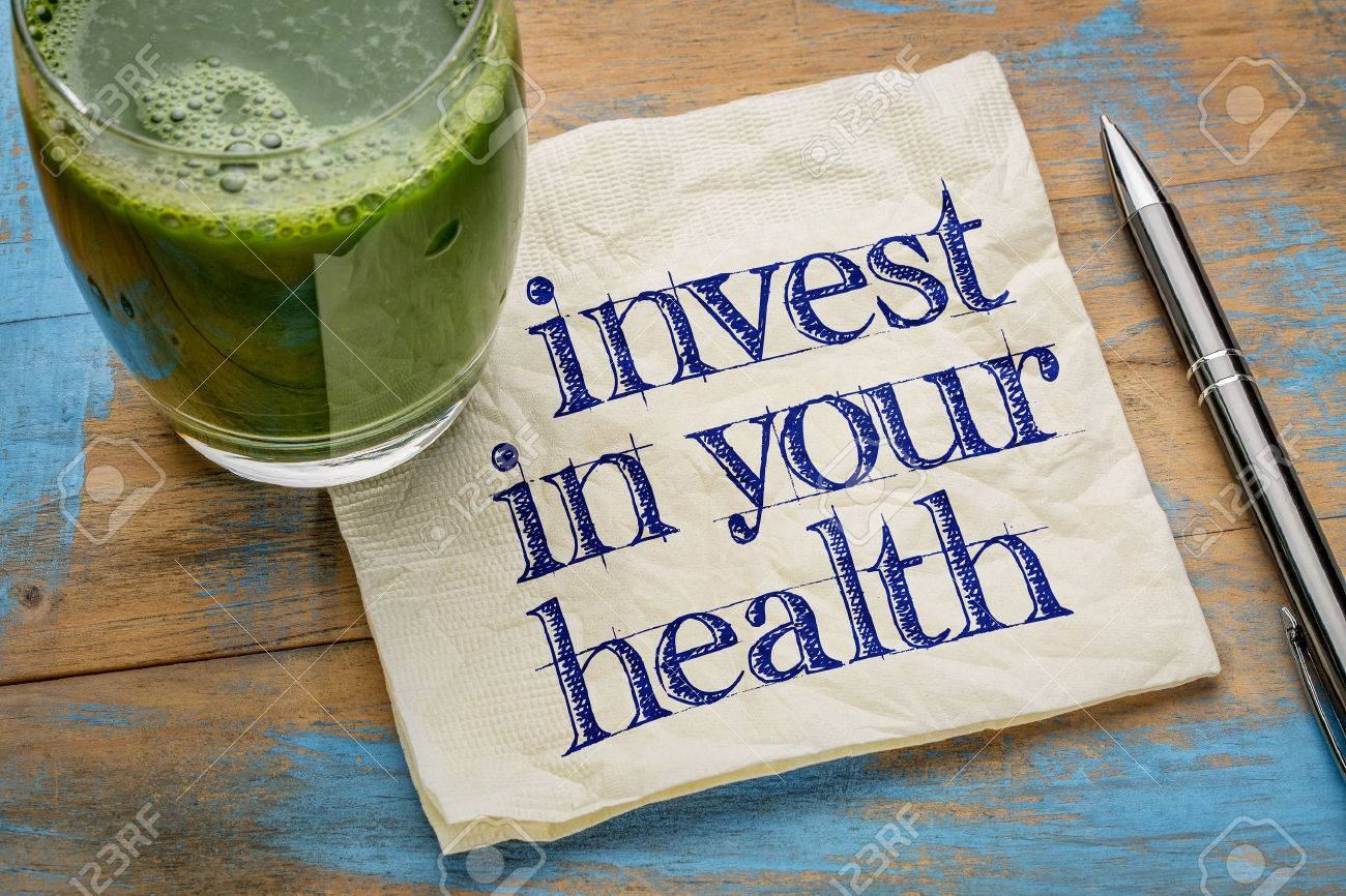 invest in your health advice or reminder - handwriting on a napkin with a glass of fresh, green, vegetable juice Stock Photo - 55759391