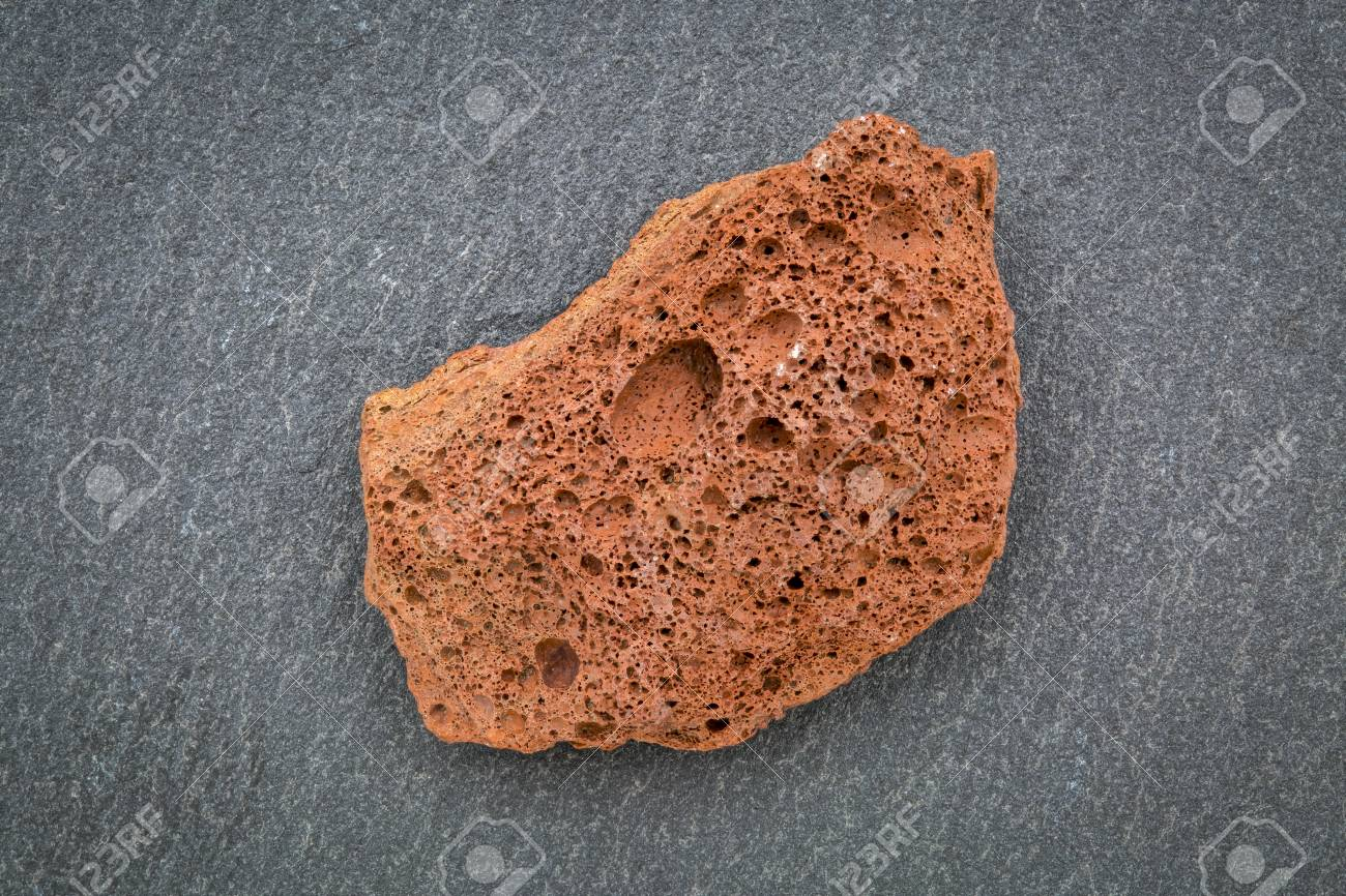 Scoria Igneous Rock Sample Against Gray Slate Stone Extrusive