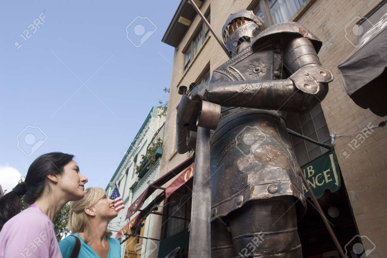 Two woman gazing at a large knight in armor Stock Photo - 931969