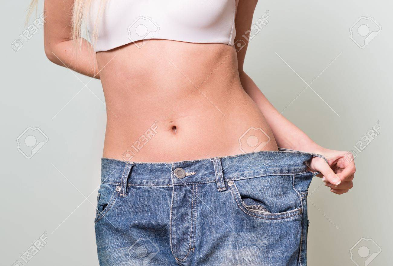 Background image too big - Close Up Of A Woman Belly In A Too Big Pants Against Grey Background Stock