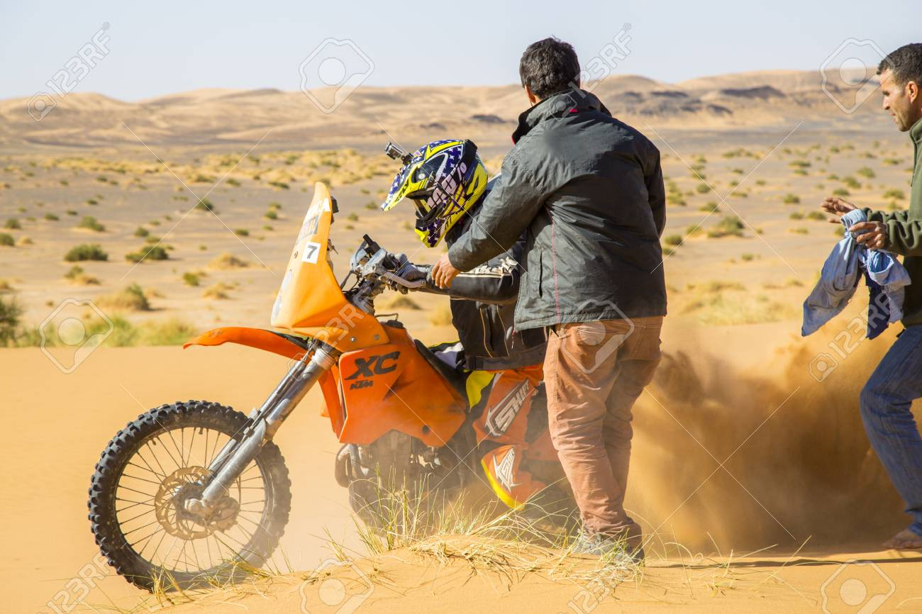 Merzouga, Morocco - February 25, 2016: A motorbike rider churns up sand as he tries to get his orange bike going in the Sahara Desert. Two men are coming to his assistance. In the distance you can see rougher terrain; sand with tufts of grass and hills - 93588231