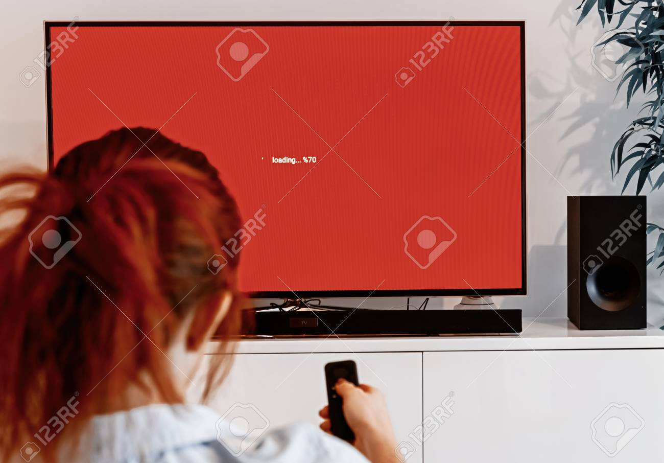 Redhead woman sitting in her living room and holding a TV remote control in front of a screen waiting message while loading an application on her connected TV - 115162264
